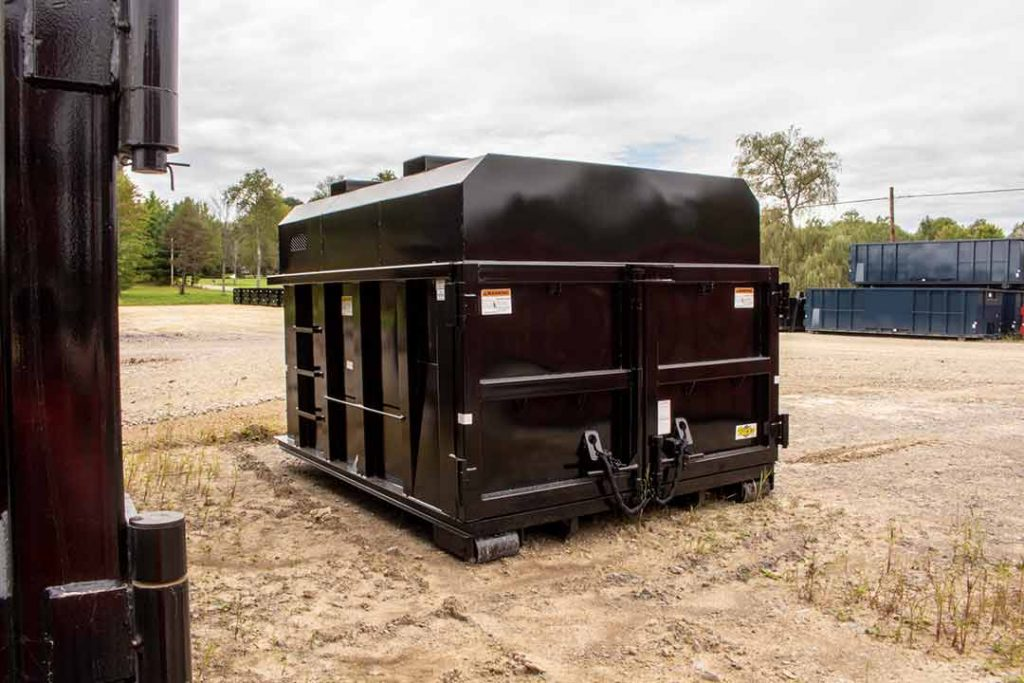 Black roll-off style chipper with an enclosed removable roof and barn doors