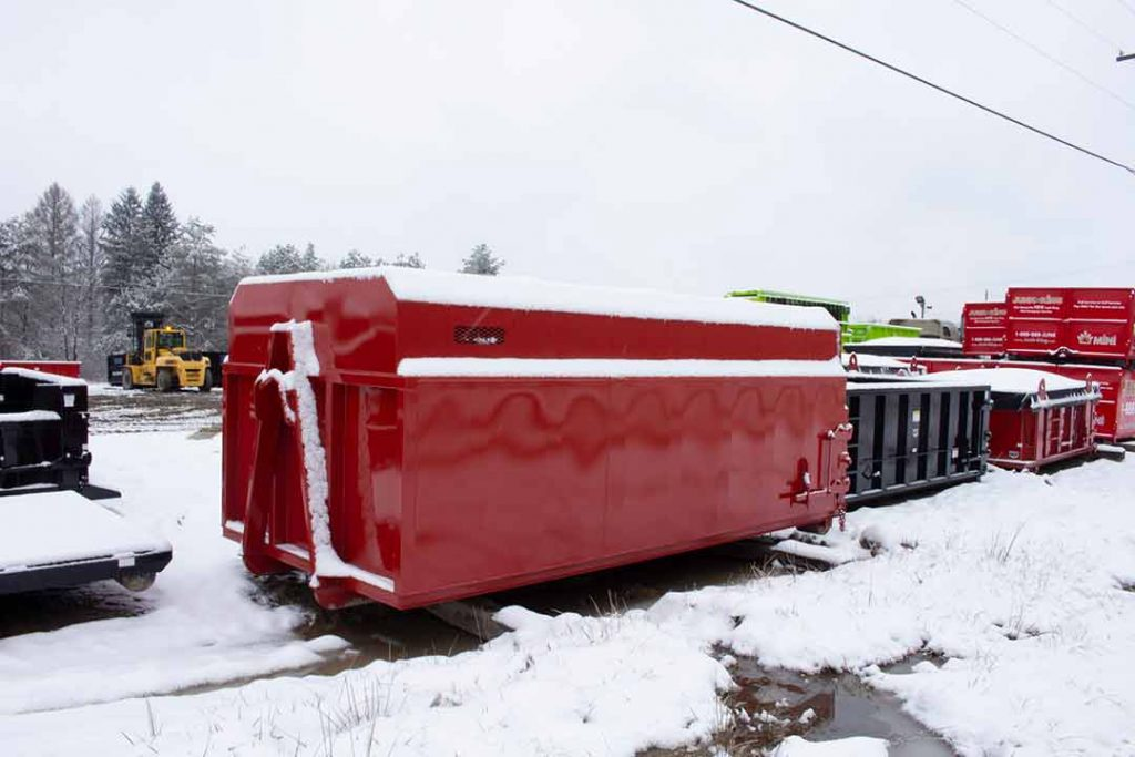 Red Chipper style roll-off container with smooth sides and hooklift hookup