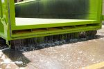 A lime green dewatering roll-off container showing how the liquid separates using the dewatering basket