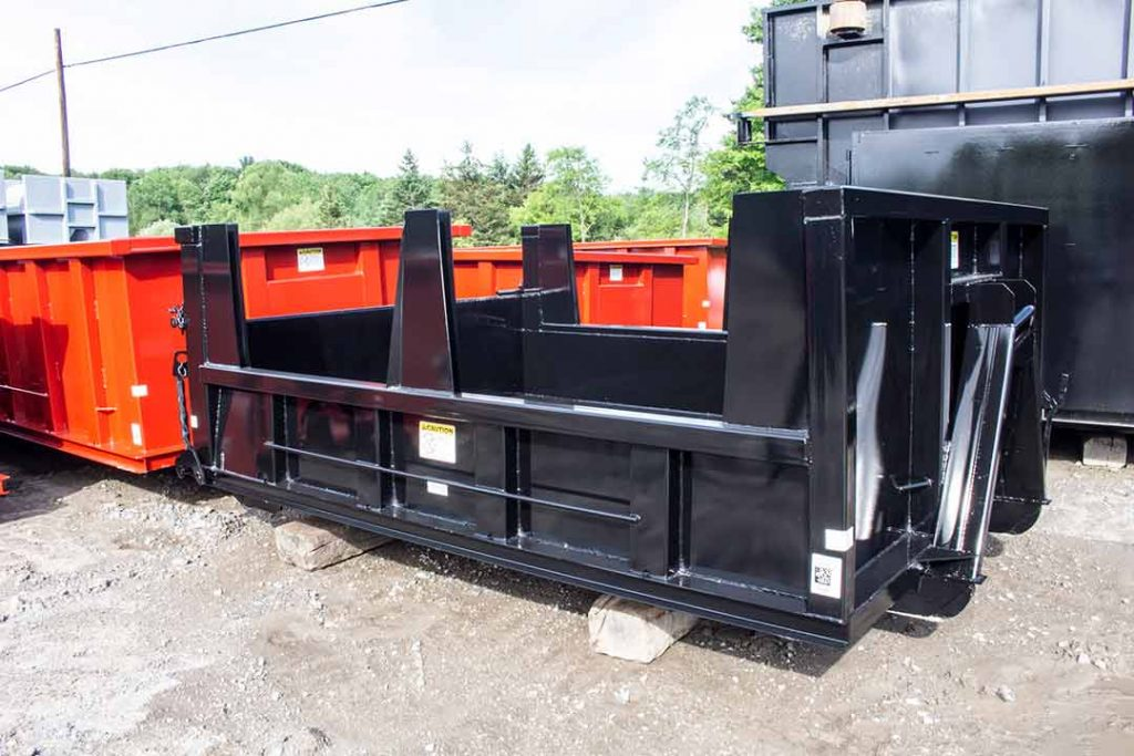 Close up Black dump body roll-off container with tall board pockets, hooklift style hookup and front release dump gate