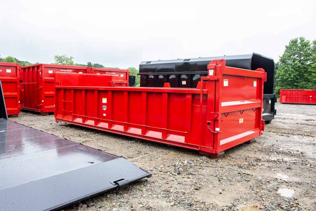 Red dump body roll-off container with taller bulkhead sheet and dump single swing style tailgate.