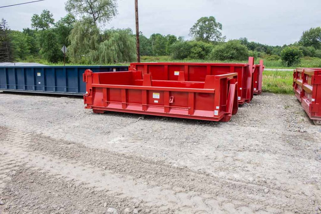 Red dump body roll-off container with hooklift hookup, dump tailgate, and board pockets