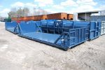 Blue flatbed roll off container with expanded cable bulkhead and standard bulkhead with exposed cable hookup