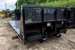 Black flatbed roll-off container with expanded metal bulkhead and cable style hookup