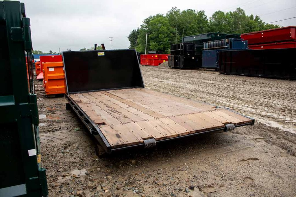 Black flatbed roll-off container featuring an apitong deck and beavertail