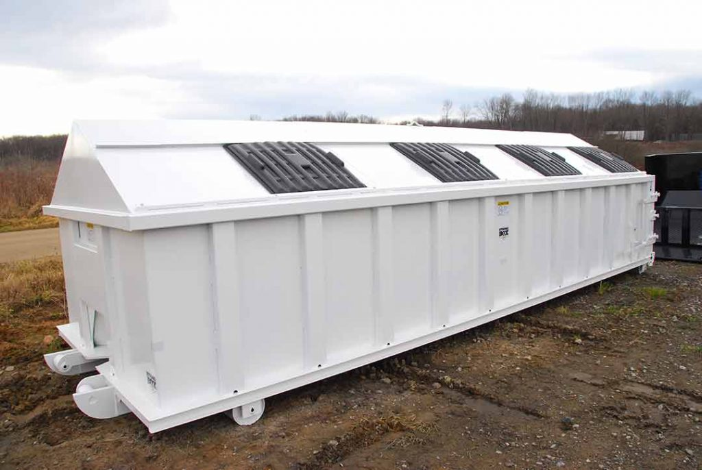 White recycler style roll off container with peak style roof, sliding lids, and cable style hookup
