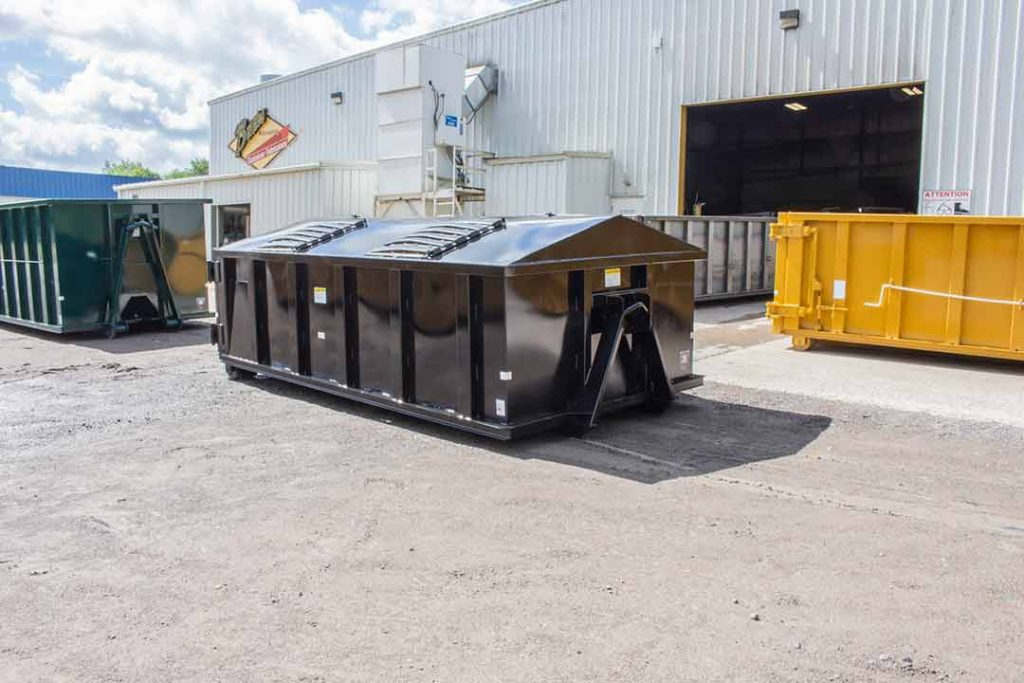 Black recycler style roll off container with peak style roof, hinged lids, and hooklift style hookup