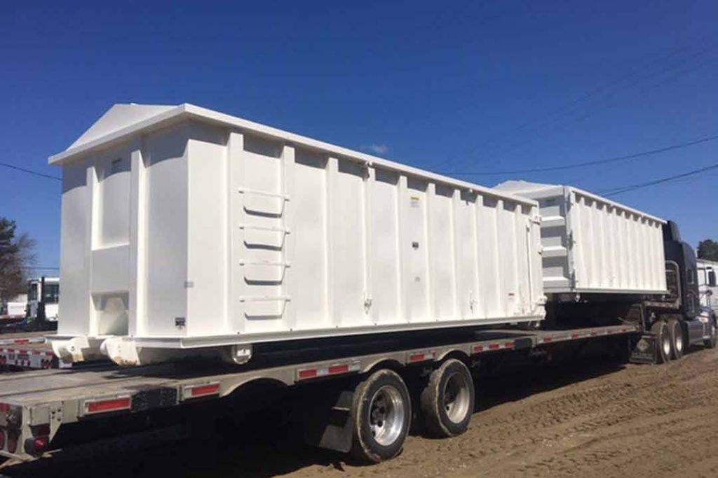 White recycler style roll off container with peak style roof, sliding lids, and cable style hookup on truck deck ready to ship