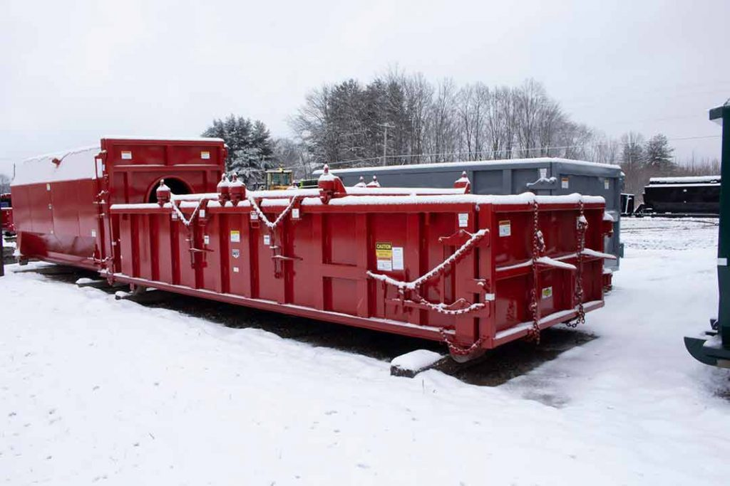 Red double rolling roof rolloff container in snow