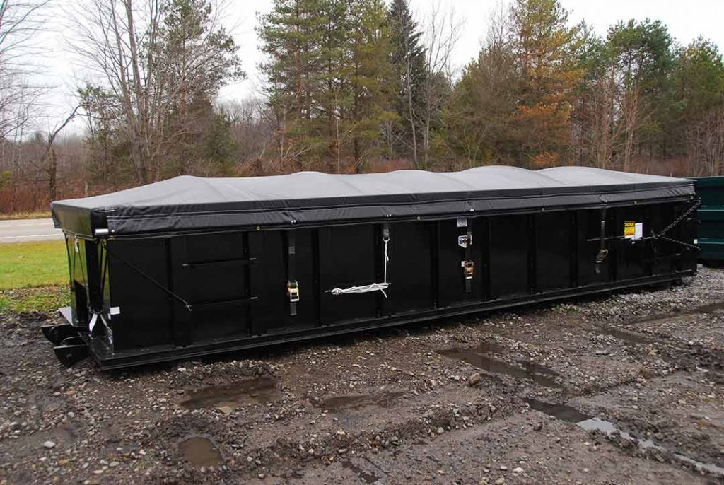 Black sealed style roll off container with side roll tarp system and cable style hookup