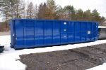 Blue sealed style roll off container with hooklift style hookup in the snow