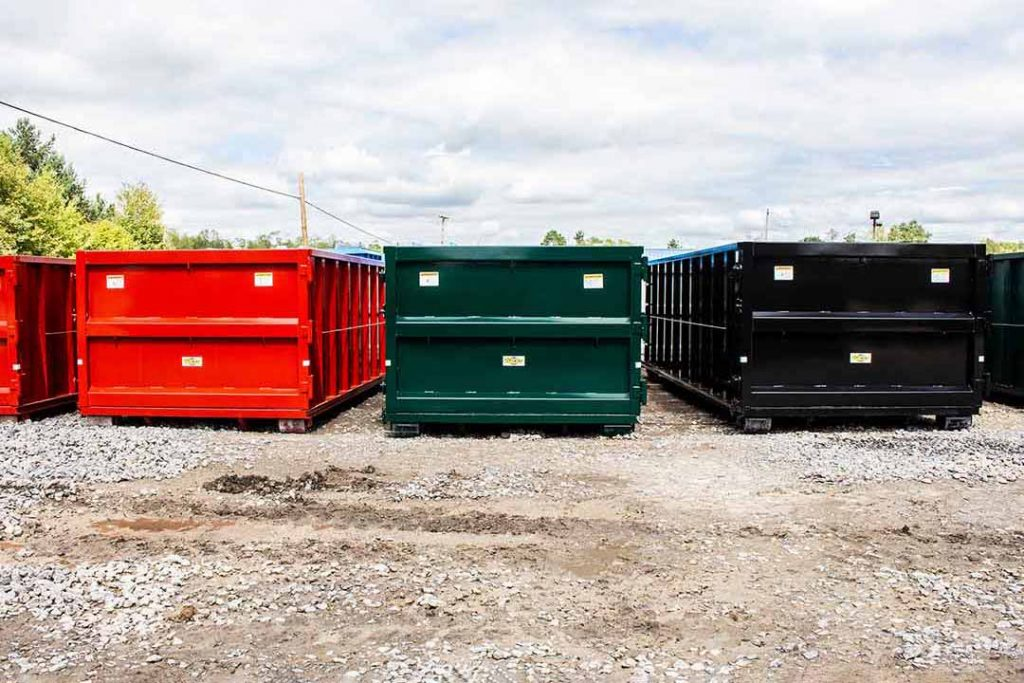 Green, red, and black Strong Box rolloff containers with single side swing tailgates