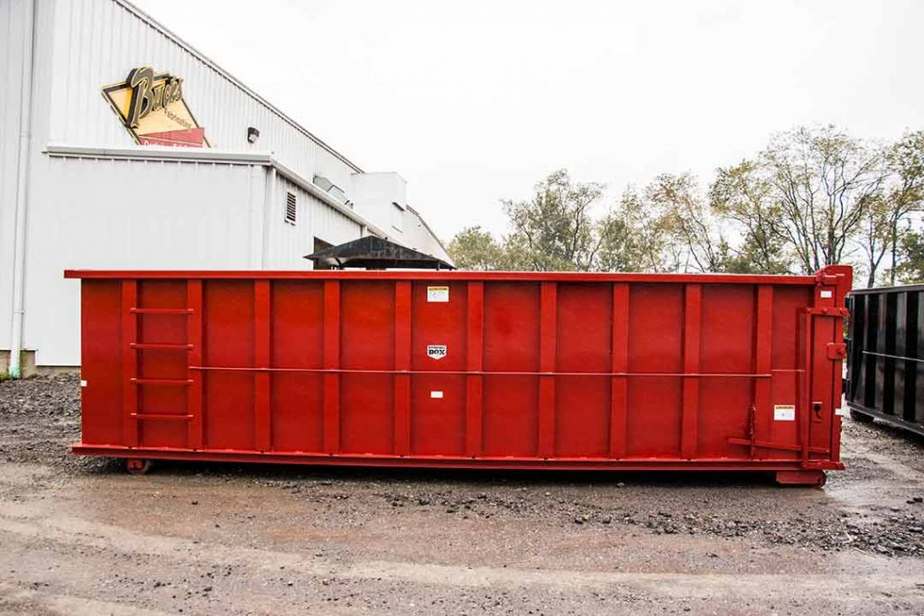 Side view of a red Strong Box rolloff container with dump single side swing tailgate