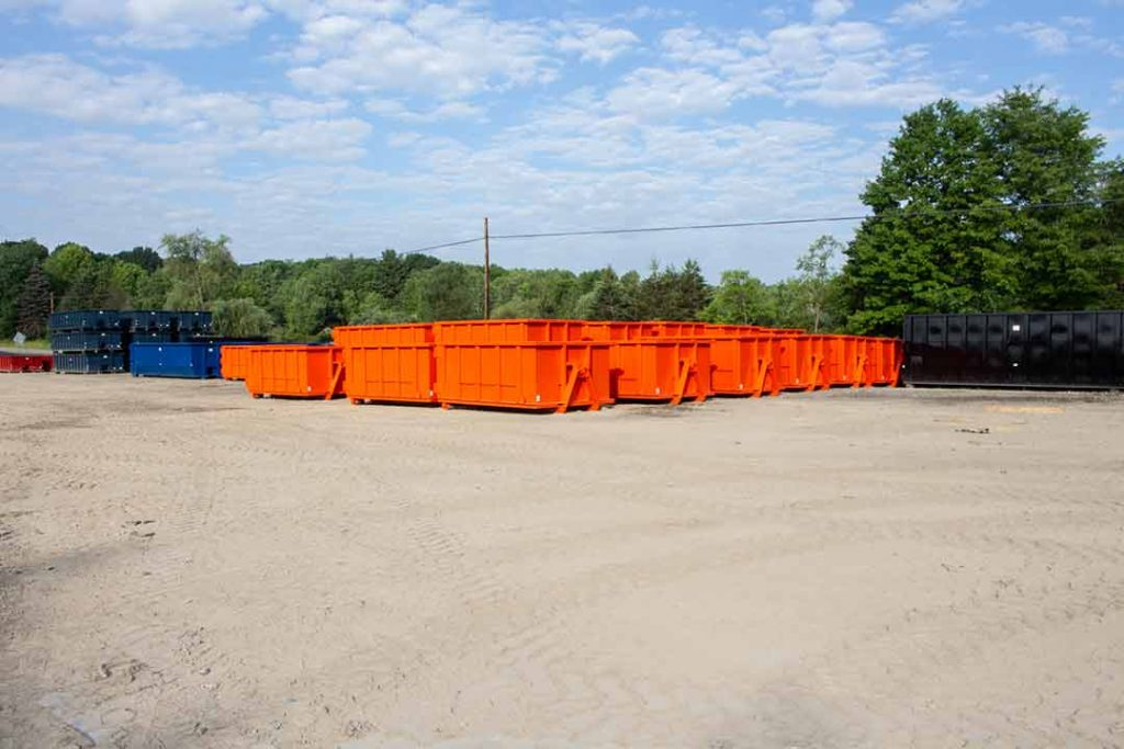 Orange Strong Box rolloff containers nested together in the yard with hooklift hookup