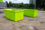 Lime green 6yd Trash Box rear load small can containers getting ready to be stacked for shipment