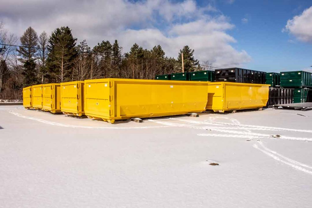 group of yellow tub style roll off containers with side swing tailgates in the snow