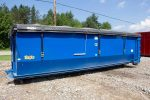Blue tub style rolloff container with side roll tarp system, cable style hookup and single side swing tailgate
