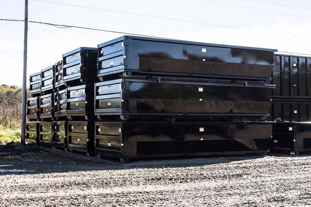 Black tub style rolloff containers with single side swing tailgate and cable hookup stacked in the yard